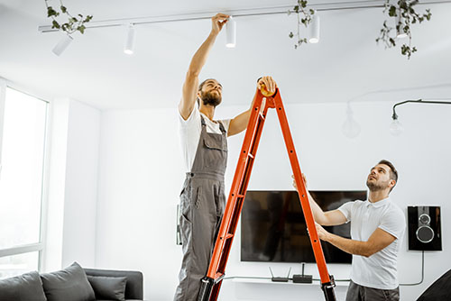 Professional electricians installing light spots, standing on the ladder in the living room of the modern apartment.