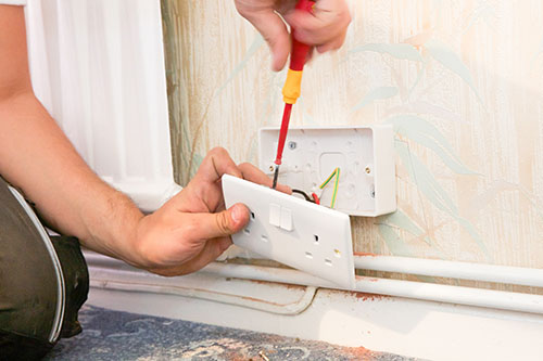 Electricians wiring a new power socket in a domestic property.